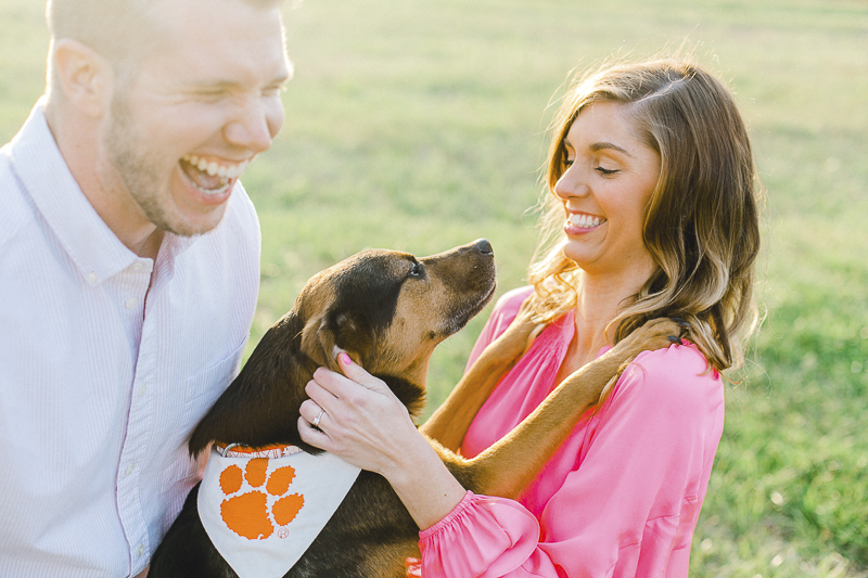 dog wearing bandanna with orange paw print hugging woman, ©Casey Hendrickson Photography | Charlotte, NC Engagement photos with mixed breed dog