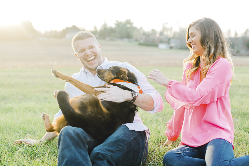 couple laughing with dog on man's lap, ©Casey Hendrickson Photography | Charlotte, NC Engagement photos with a dog