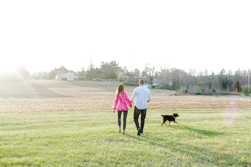 couple walking hand in hand with dog running along them | ©Casey Hendrickson Photography | Charlotte, NC Engagement photos with a dog