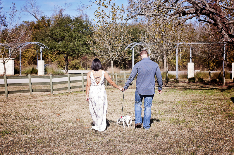 couple walking their puppy | ©Kelly Urban Photography | dog friendly engagement photos, Richmond, Texas