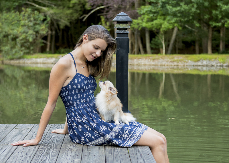 bond between dog and human, long haired Chi sitting in teen's lap on dock ©Trina Bauer Photography | Dog-Friendly senior portraits