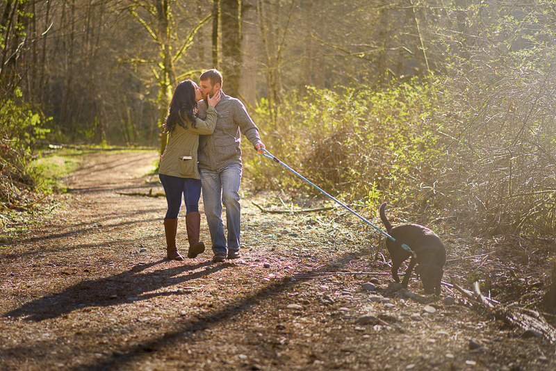 couple walking dog and kissing on trail, ©Lavender Bouquet Photography | dog friendly engagement portraits