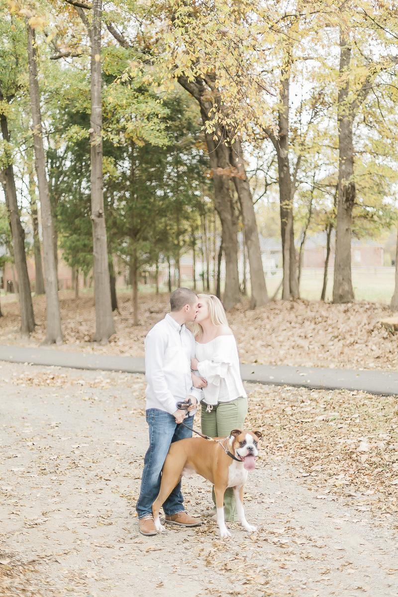 dog friendly engagement session, Charlotte, NC, couple kissing while walking dog | ©Casey Hendrickson Photography
