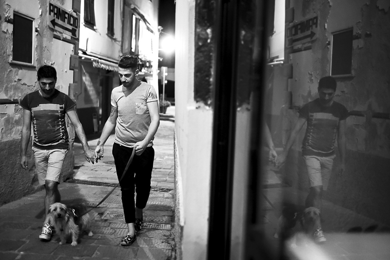 black and white engagement portrait, 2 men holding hands walking their dog through small Italian village
