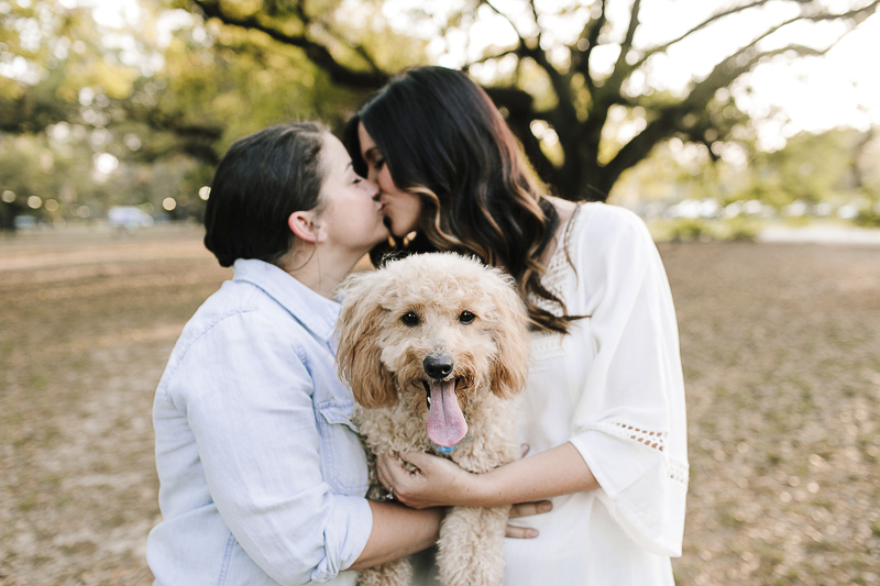 two women kissing while holding their dog, outdoor engagement photos, ©Theresa Elizabeth Photography | dog-friendly engagement session, New Orleans,