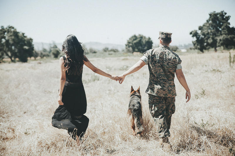 couple holding hands following dog through the field, dog-friendly family photo session | ©Wanderlust Photography