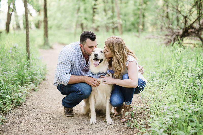 couple kneeling down and kissing their Golden Retriever, ©Zoe Life Photography | dog friendly engagement photos with Golden Retriever, Castlewood State Park, MO