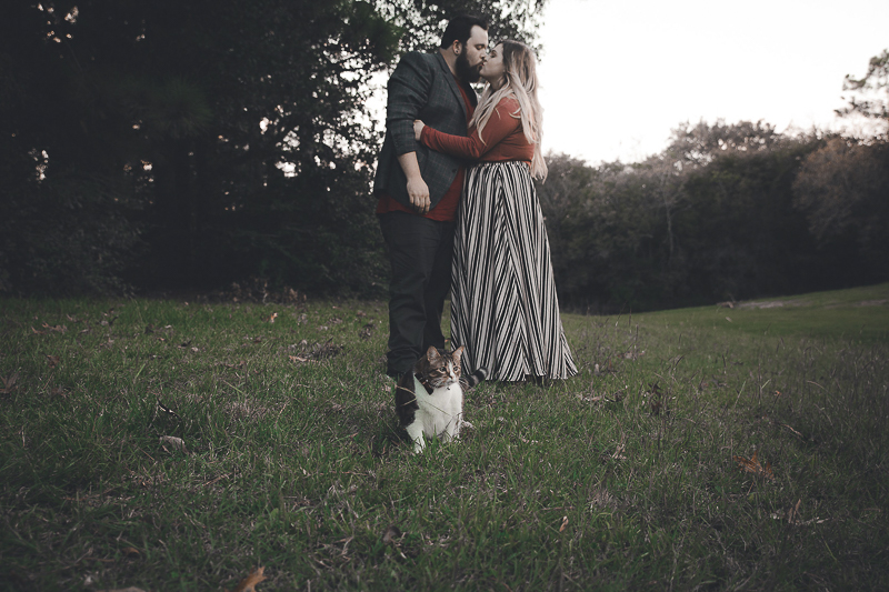 couple kissing while standing, cat sitting in front of them, ©Admyer Studios | cat-friendly engagement photos