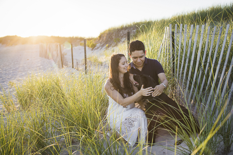 New England engagement photography, couple and their dog sitting in front of dune fence Trish Kemp Photography