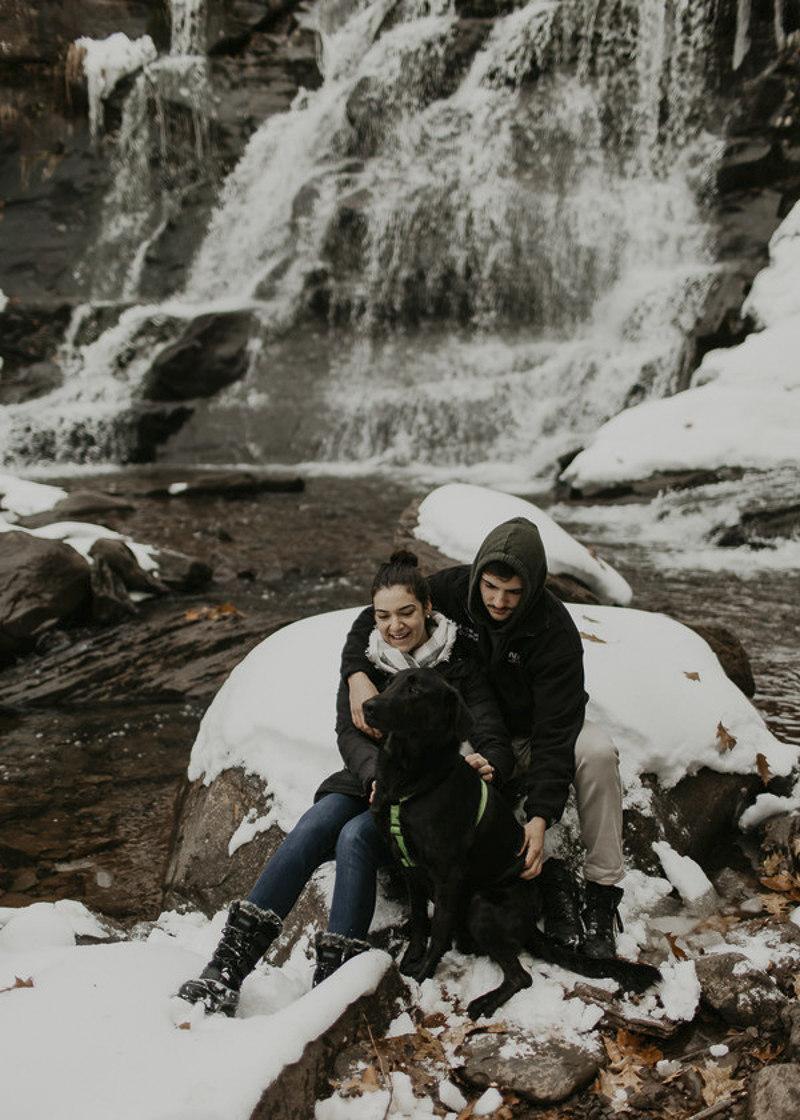 couple and their dog sitting on snow covered boulder in front of waterfall ©Belle La Vie Images | Hudson Valley dog friendly engagement photos