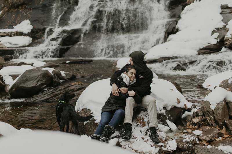 dog looking at waterfall while couple snuggles on boulder, winter engagement session | ©Belle La Vie Images