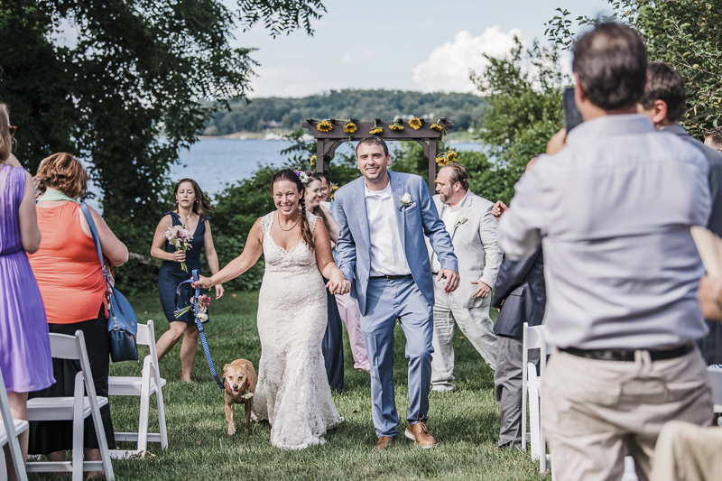 Just married bride, groom and dog walking up the aisle
