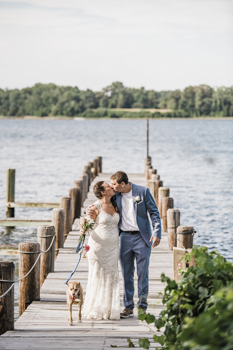 bride and groom kissing on dock with dog at side | ©Landrum Photography