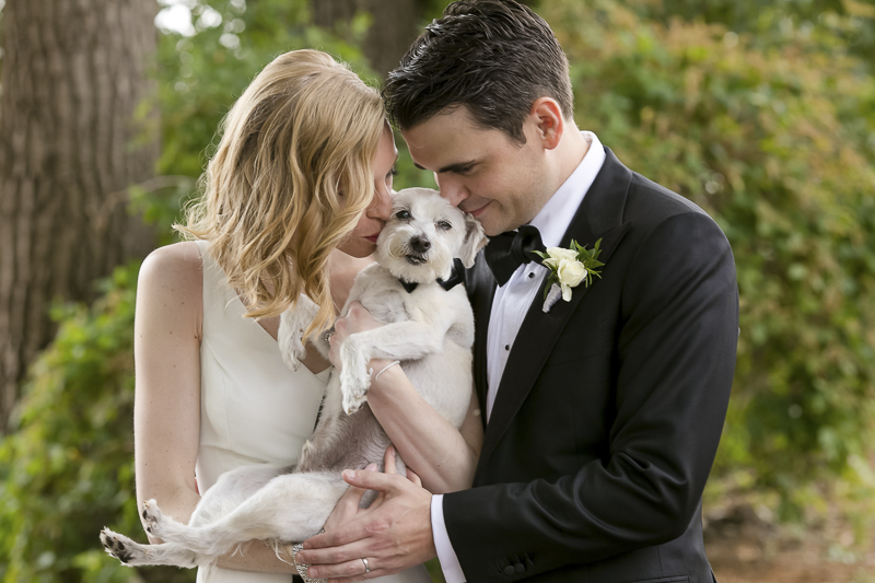 bride and groom kissing their dog | wedding photos with dogs, ©Jeannine Marie Photography -dog-friendly wedding photographer