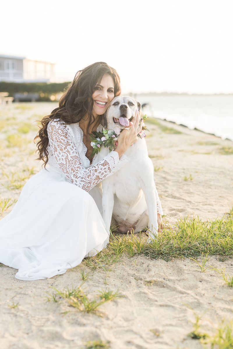 woman wearing long white dress cuddling with senior dog on the sand, NJ lifestyle pets and people photography | ©Kelly Sea Images