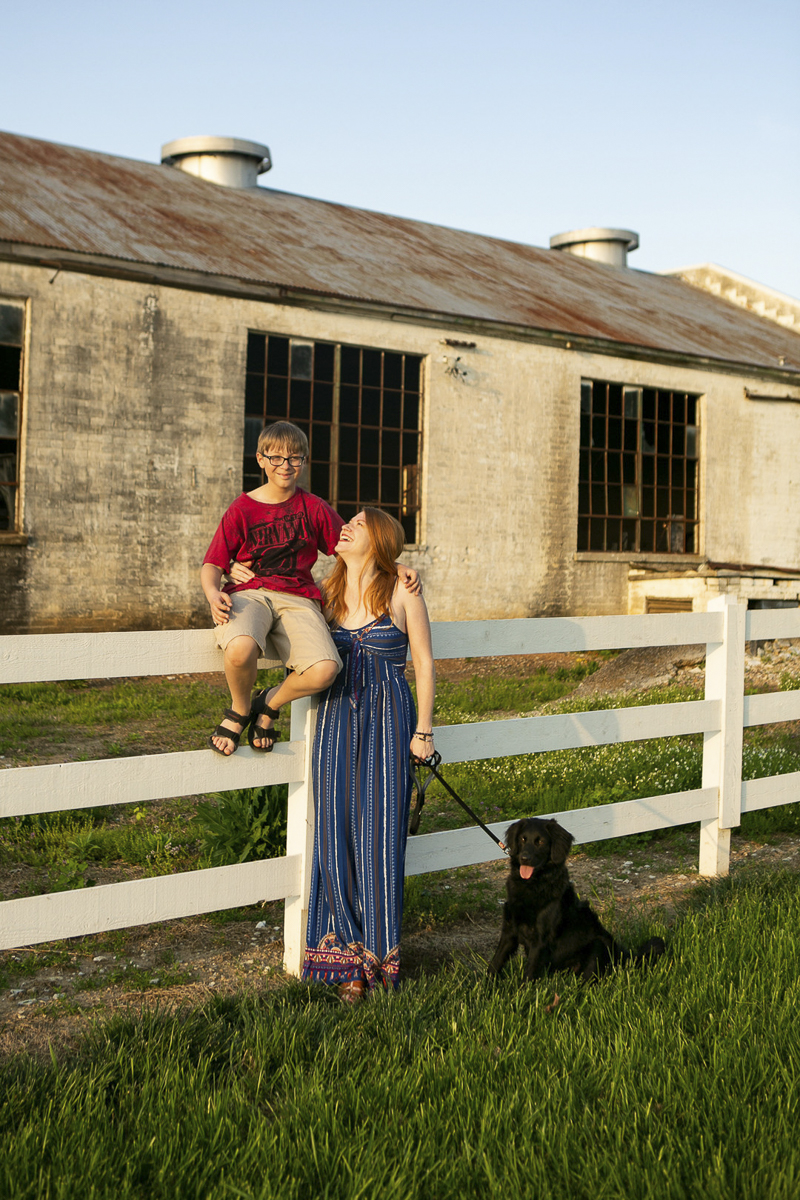boy sitting on a fence, mom looking at him, puppy sitting on the ground, family portraits with pets, ©Mandy Whitley Photography