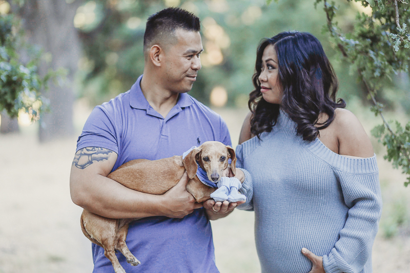 couple looking at each other, man holding Doxie, ©Kathy Izzy Photography, Sacramento and Bay Area maternity photography
