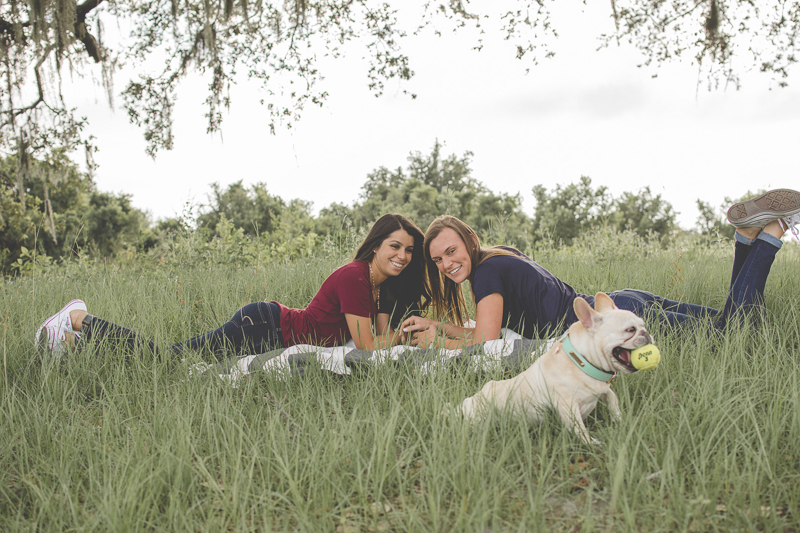 couple lying on blanket looking at Frenchie with tennis ball, ©Kimberly Santana Photography-dog-friendly summer engagement portrait session