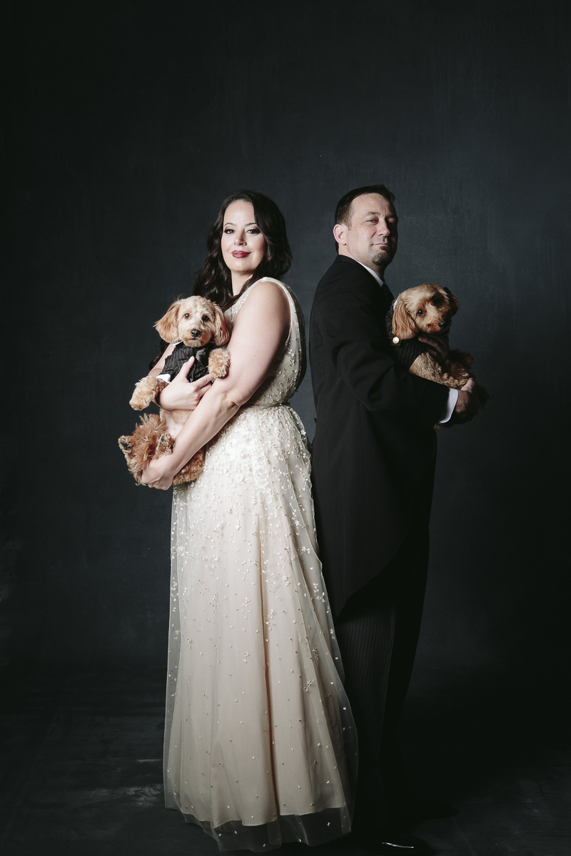 couple in formal wedding attire holding small brown dogs, ©Nicole Caldwell Photography | engagement photography with dogs, Orange, CA