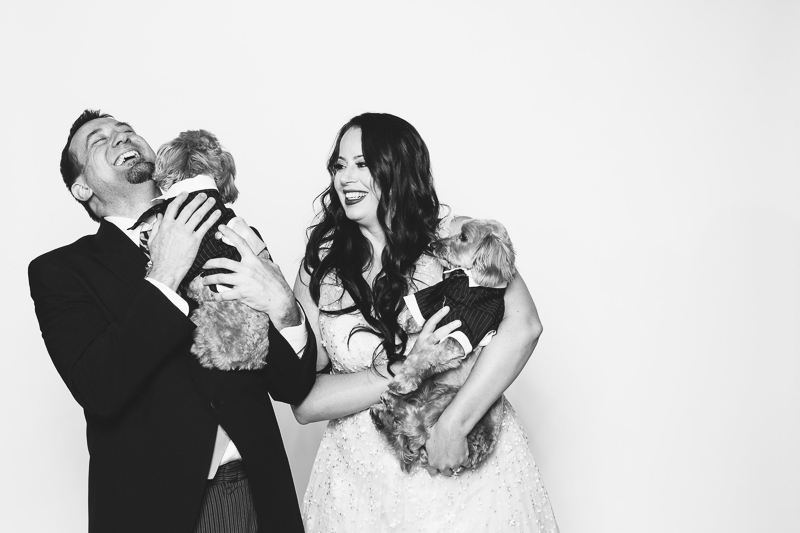 man and woman holding their dogs who are wearing tuxedos, fun engagement photo ideas | ©Nicole Caldwell Photography |