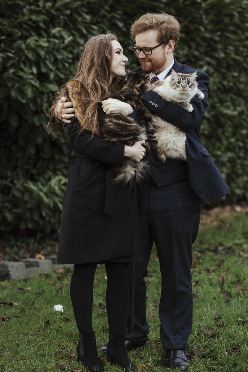 couple looking at each other while holding their cats, Ragdoll cat looking at photographer | ©Olga Hogan Photography