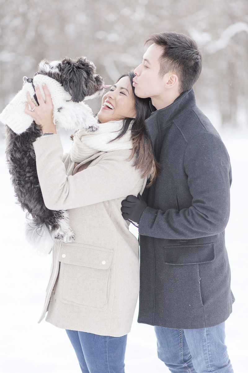 woman holding dog up during winter engagement portraits, couple looking at their Shih Tzu mix, winter engagement session | ©Rebecca Sigety Photography
