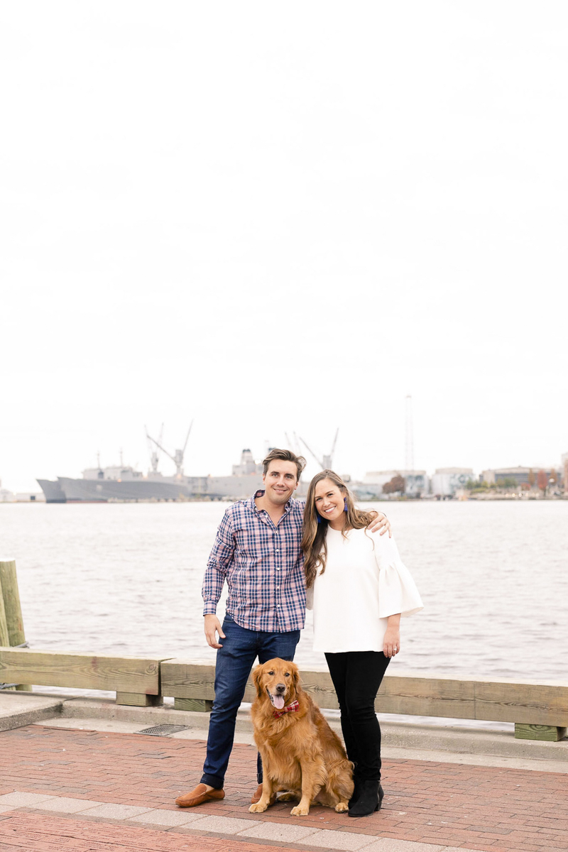 Golden Retriever sitting on pier between engaged couple, ©Amanda McPhee Studios-dog-friendly engagement, Fells Point