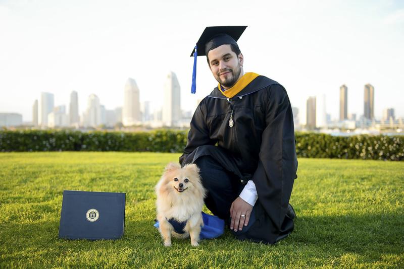 Graduation photos with a dog, man wearing cap and gown next to Pomeranian and diploma, Coronado, CA