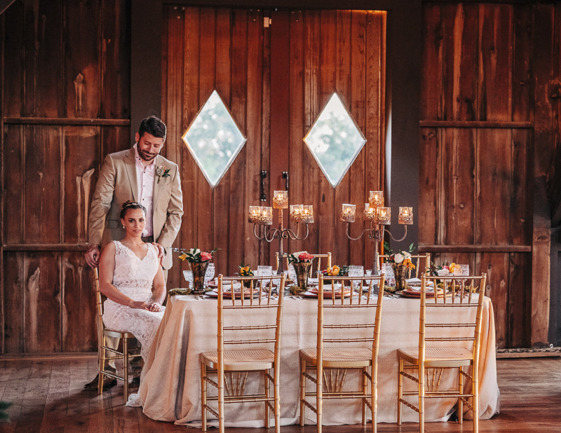 Barn at Bohemia Outlook decorated for a wedding reception, bride and groom sitting at table, Landrum Photography
