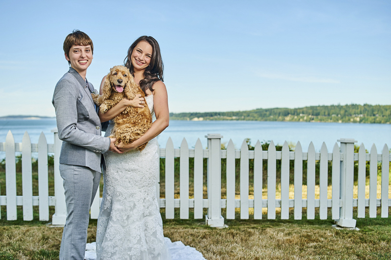 dog friendly LGBTQ wedding couple holding their dog in front of white picket fence, ©Lavender Bouquet Photography
