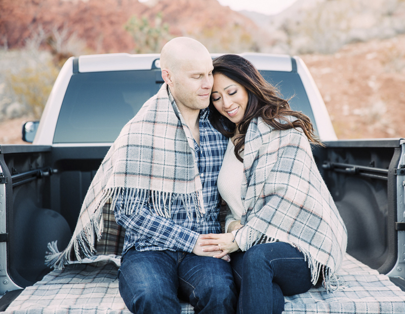 couple sitting in bed of pickup truck with blanket around them, romantic engagement photos   ©Alycia Moore Photography