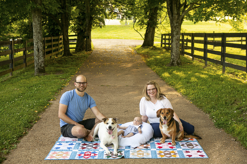 couple, baby, dogs sitting on quilt on path ©Mandy Whitley Photography | Nashville Pet and Family Photographer