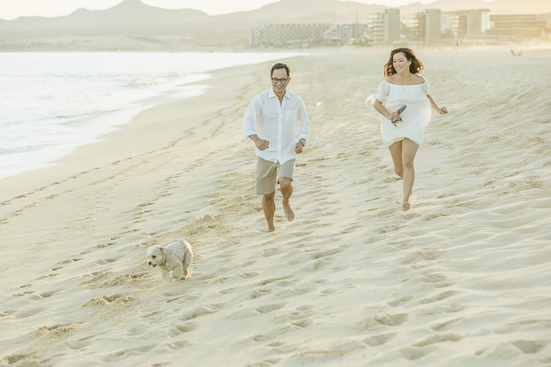 couple and their dog running on sandy beach, ©Daniel Jireh Photographer | lifestyle dog photography Cabo San Lucas, Mexico