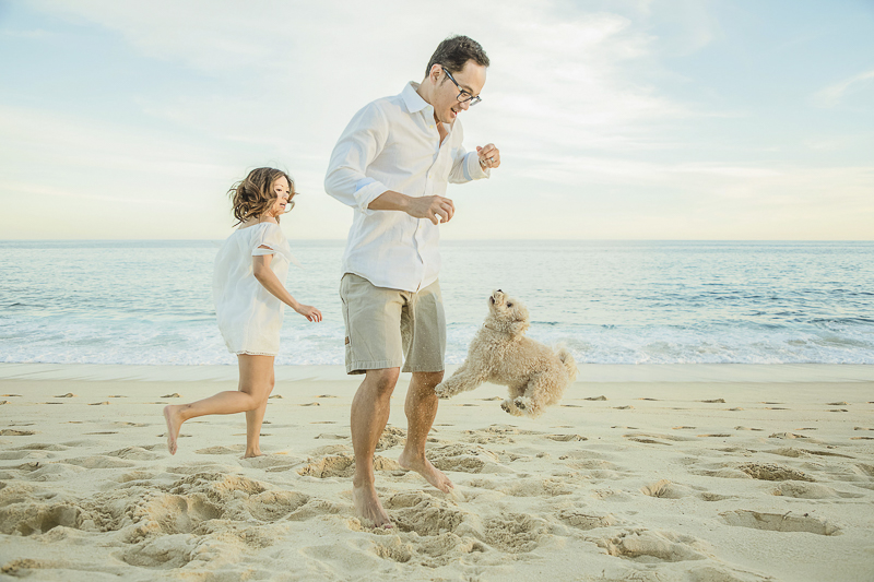 couple playing with their small white dog at the beach | ©Daniel Jireh Photographer | lifestyle family photography Cabo San Lucas, Mexico