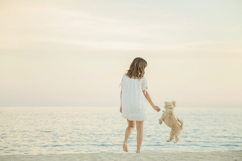 woman's best friend, girl and her dog playing at the beach