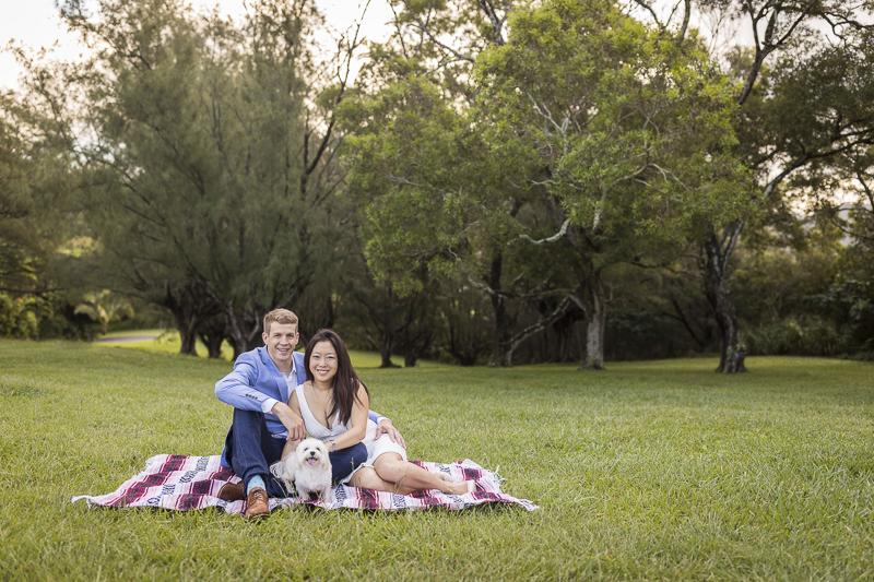 small white dog and family sitting on blanket, Honolulu engagement photos, VIVIDfoto