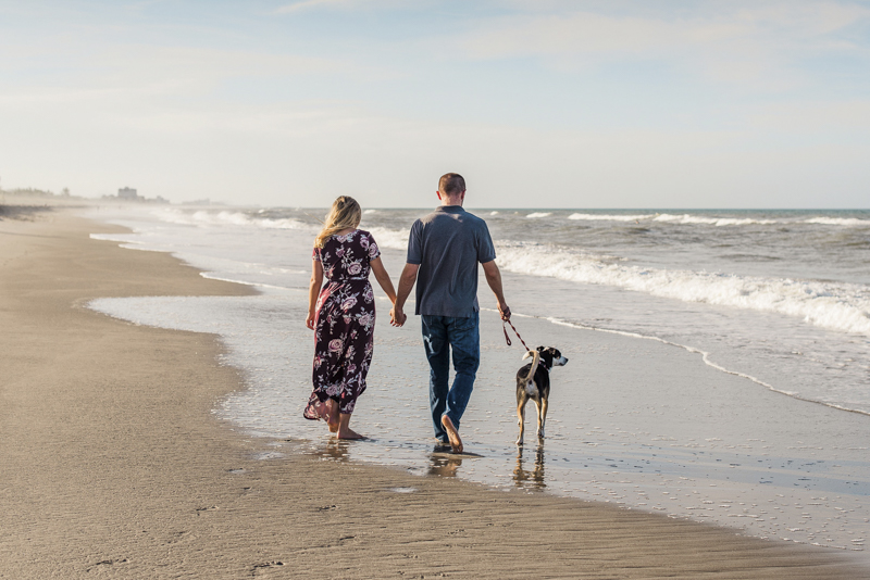 Beach engagement photos with a Collie Heeler mix, couple and their dog walking on the beach, ©Liz Cowlie Photography