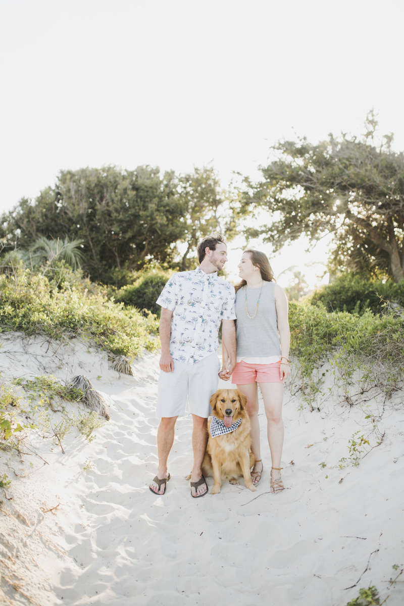 engaged couple and their dog in the sand, ©Rainey Gregg Photography | St. Simons Island, Georgia