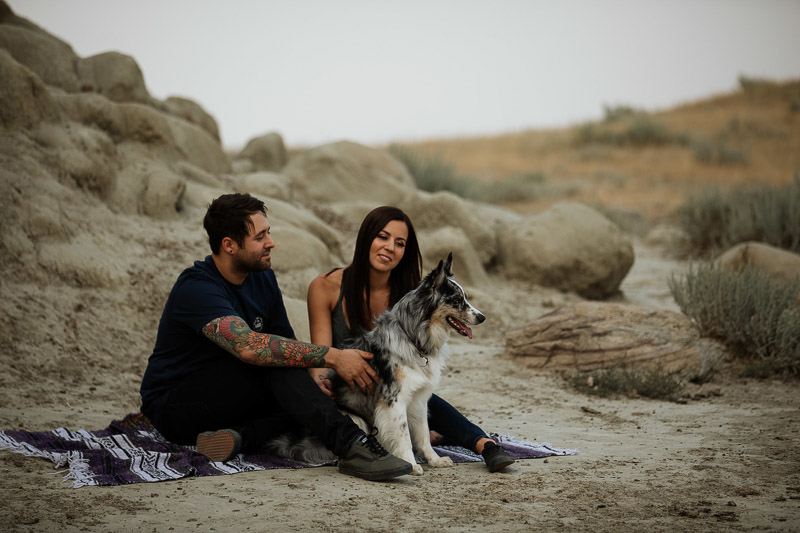 couple and their Aussie mix dog sitting on a blanket, dog-friendly engagement inspiration, ©Jackie Hall Photography | dog-friendly engagement portraits, Big Muddy Valley, SK, Canada