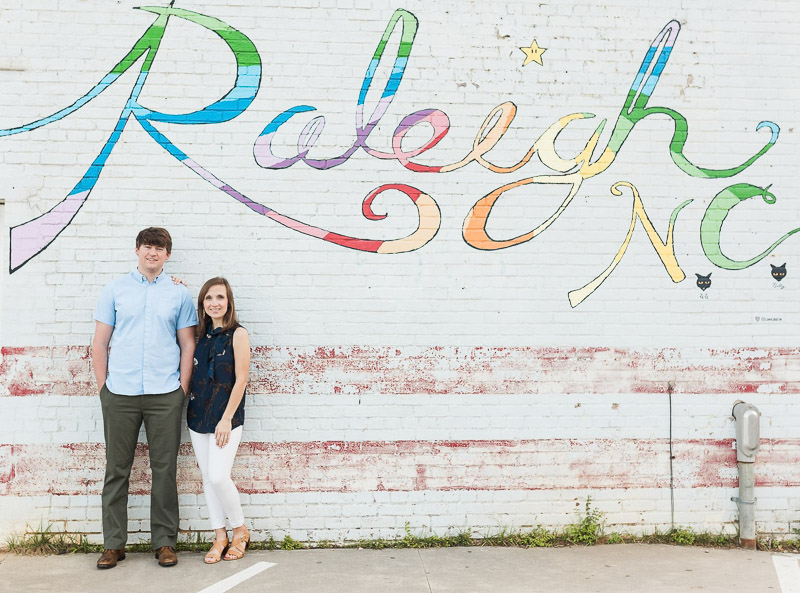 couple standing in front of Raleigh, NC mural, engagement session