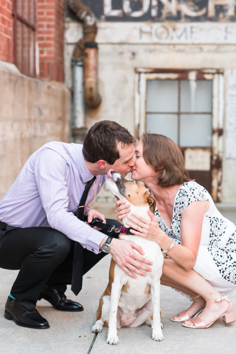 collie mix licking man's face while he kisses his fiancee, © Michelle and Sara Photography | American Tobacco Campus dog-friendly engagement photos