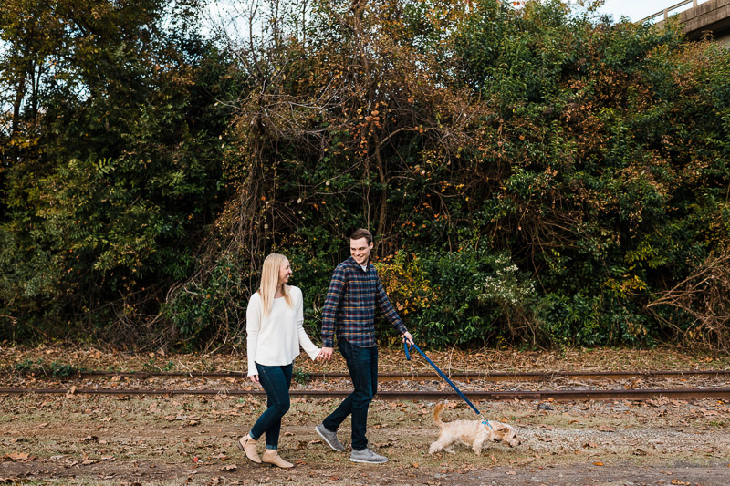 couple walking little dog next to rail road tracks, ideas for dog-friendly engagement photos, ©Easterday Creative