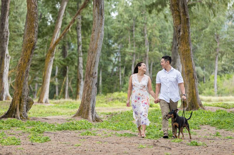 engaged couple and their small dog walking, ©VIVIDFotos | dog-friendly engagement photos, Waimanalo, Hawaii