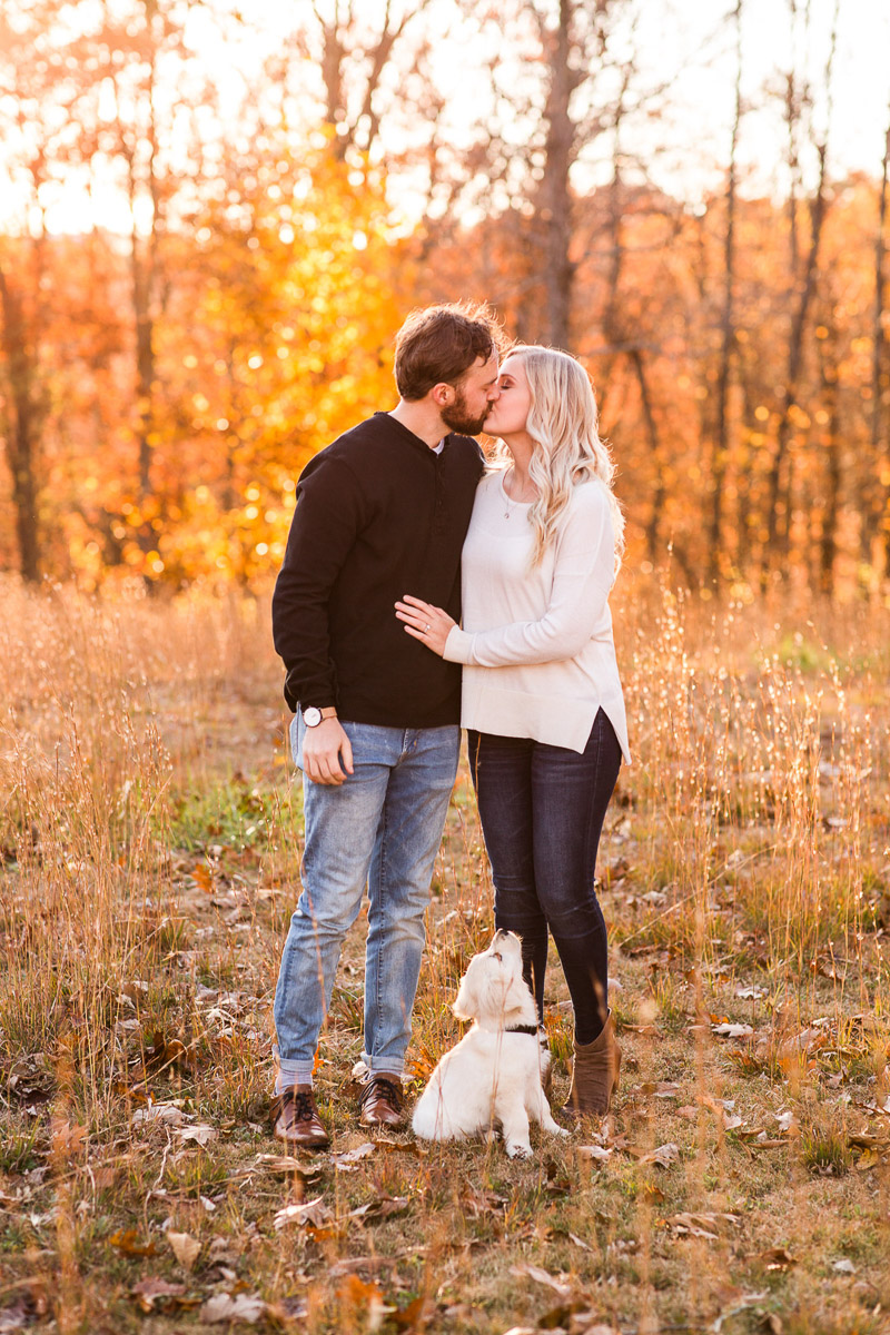 Puppy looking up at couple who are kissing, fall anniversary photos, ©Katelyn Workman Photography