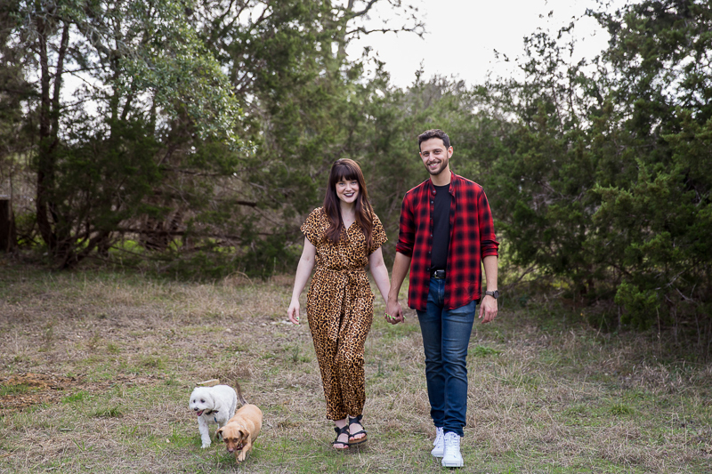 couple walking hand in hand with their small dogs, dog-friendly engagement ideas | ©Wildflower Barn Photography