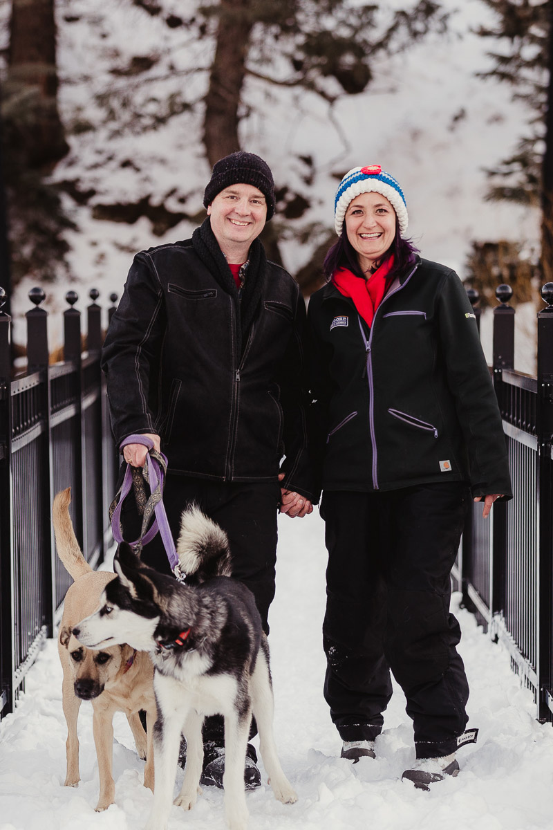 couple holding hands while walking dogs in the snow, dog photography ideas | ©Good Morrow Photography