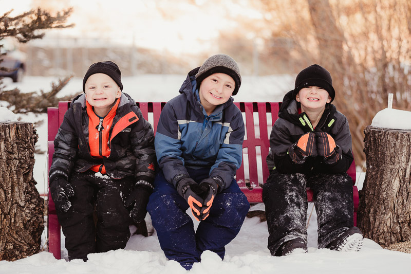 winter family portrait ideas, kid friendly family session, 3 boys sitting on snowy bench | ©Good Morrow Photography