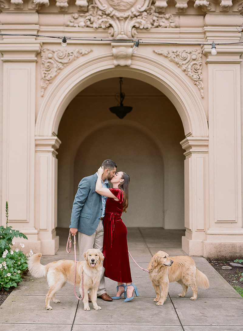 couple kissing in Balboa Park, dog-friendly engagement photos | ©The Ganeys