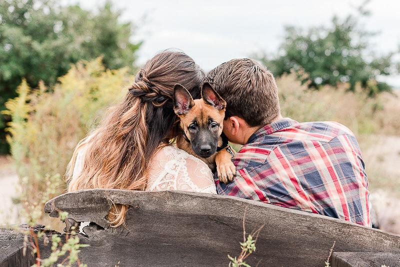 couple sitting on a bench with Belgian Shepherd puppy between them ©Catherine Crane Photography | Virginia Beach, VA