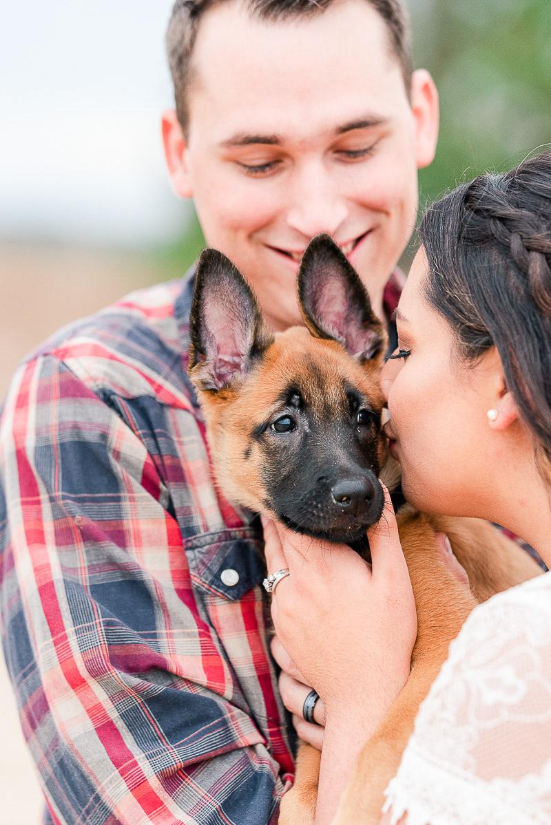 woman kissing Belgian Malinois Shepherd puppy | ©Catherine Crane Photography